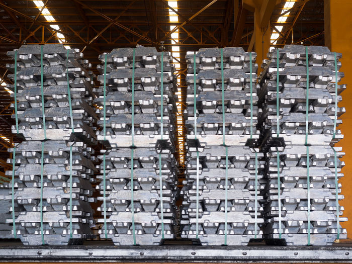 Stack of raw aluminum ingots in warehouse. Abundance Aluminum Automotive Day Distribution Warehouse Equipment Export Forklift Foundry Freight Transportation Handling Import Indoors  Industry Ingot Large Group Of Objects Lifting Metal Industry Recycling Center Shipping  Silver  Stack Stack Storage Warehouse