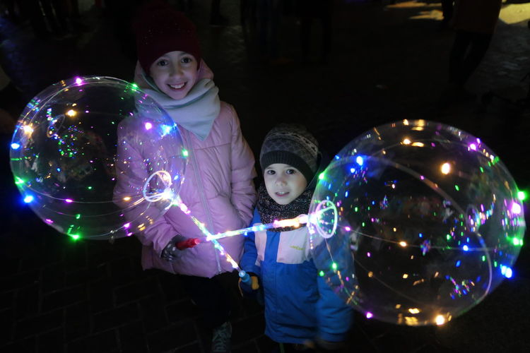 Portrait of siblings holding illuminated balloons at night during winter