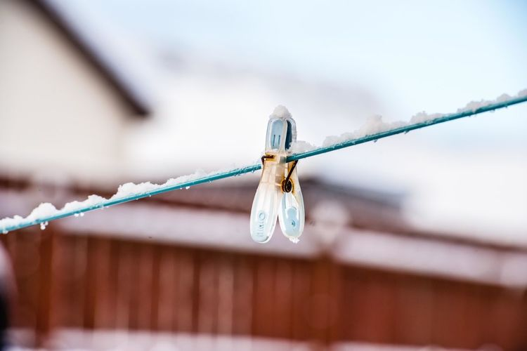 Close-Up Of Clothespin Hanging On Frozen Clothesline During Winter