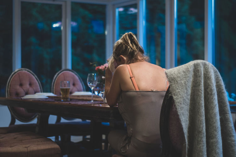 Rear view of woman sitting on table at restaurant