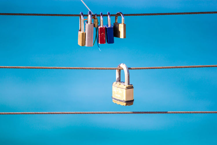 Low angle view of padlocks on steel cable against blue sky