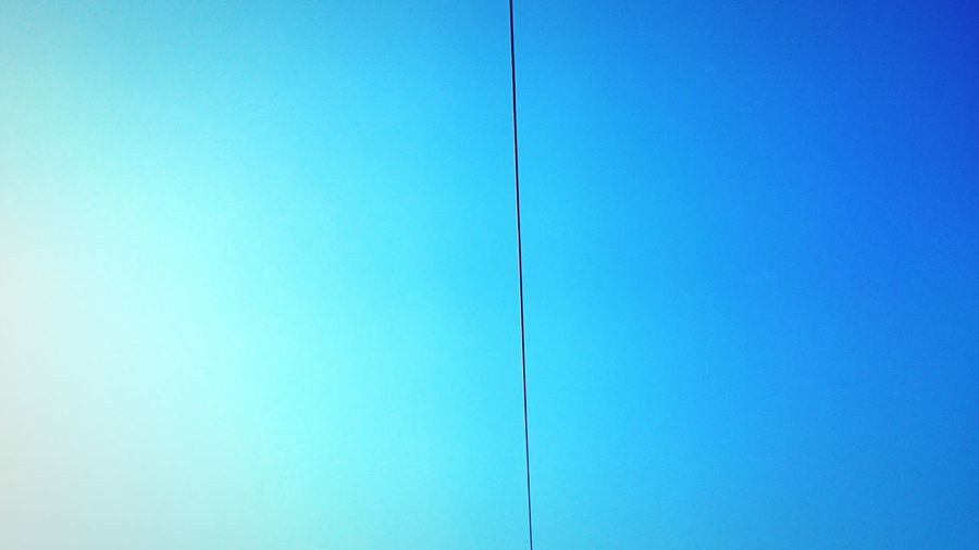Low angle view of cable against clear blue sky