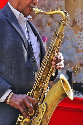 Midsection Of Senior Male Musician Playing Saxophone Outdoors
