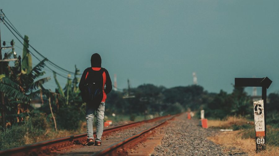 Rear view of man on railroad tracks against clear sky