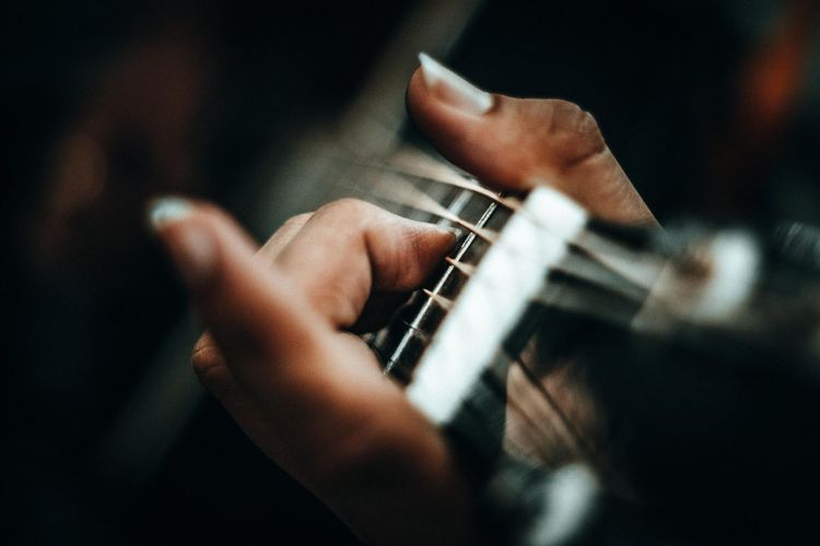 Close-up of cropped hand playing guitar