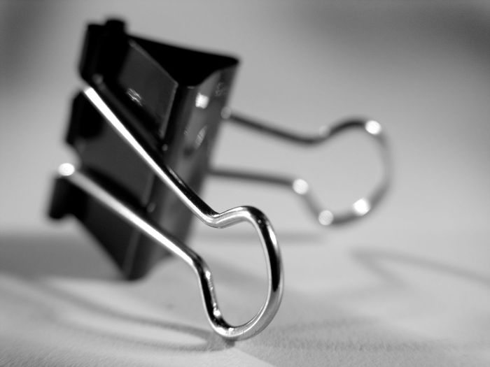 Close-up of a paper clip over white background
