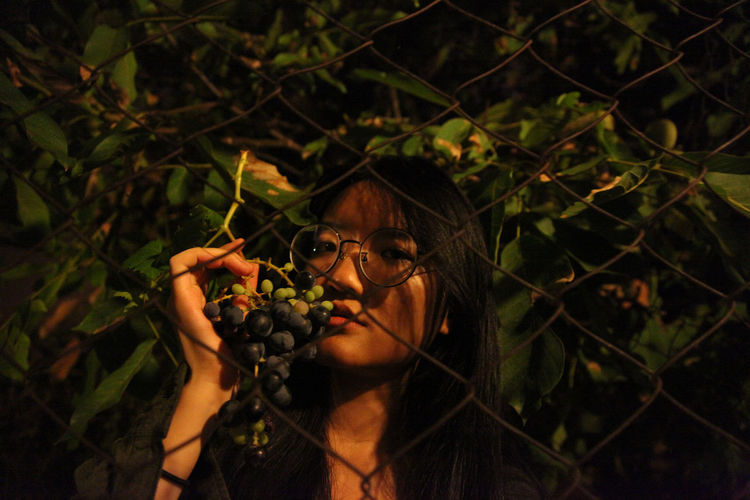 Portrait Of Woman Holding Grapes While Standing Against Chainlink Fence