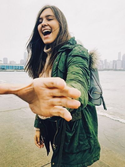 Cheerful Young Woman Gesturing While Standing At Beach