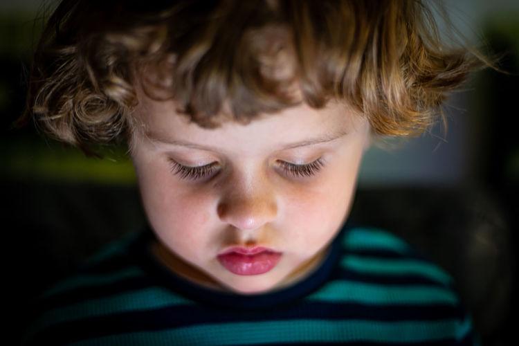 Close-up portrait of cute boy screen time