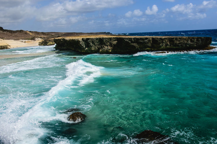 Aruba Power Aquatic Sport Beauty In Nature Day Horizon Horizon Over Water Idyllic Land Motion Nature No People Ocean Outdoors Power In Nature Rock Rock - Object Scenics - Nature Sea Sky Solid Turquoise Colored Water Wave Waves