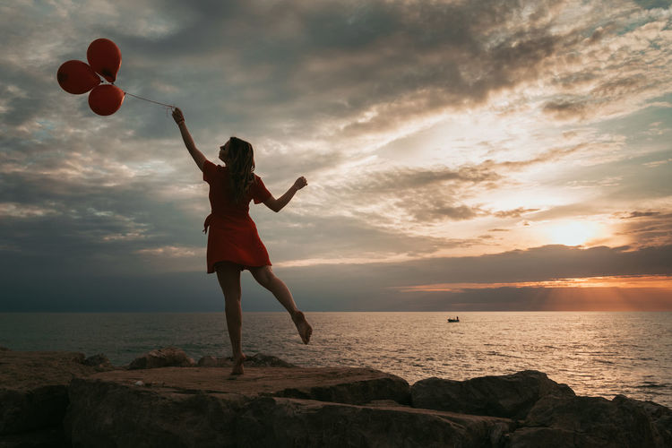 Full length of woman standing on rock at beach during sunset