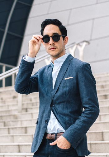 Portrait of well-dressed businessman wearing sunglasses in city
