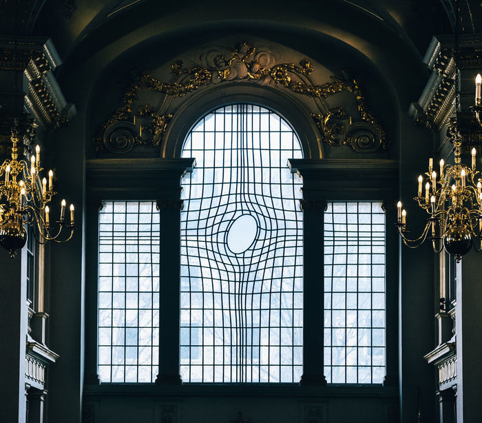 LOW ANGLE VIEW OF ORNATE GLASS WINDOW IN BUILDING
