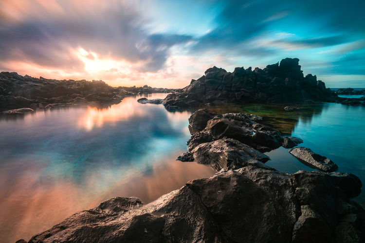 Scenic view of rocks in lake against dramatic sky during sunset