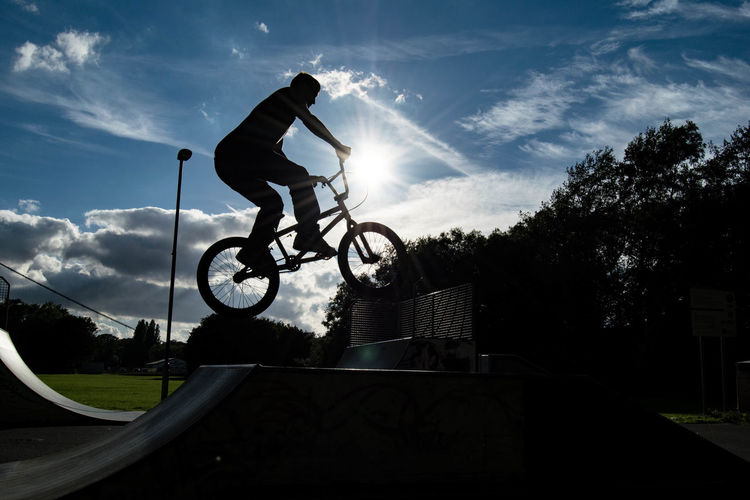 Silhouette Man Performing Stunt With Bmx Cycle At Skateboard Park Against Sky