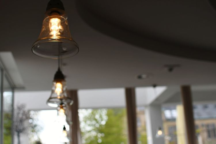 Low angle view of illuminated light bulb in building