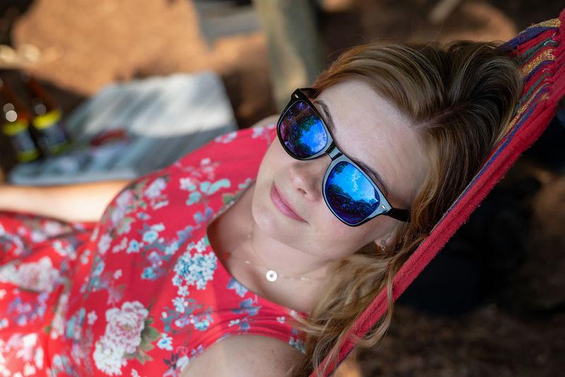 Outdoor portrait of woman relaxing in the hammock in the summer garden