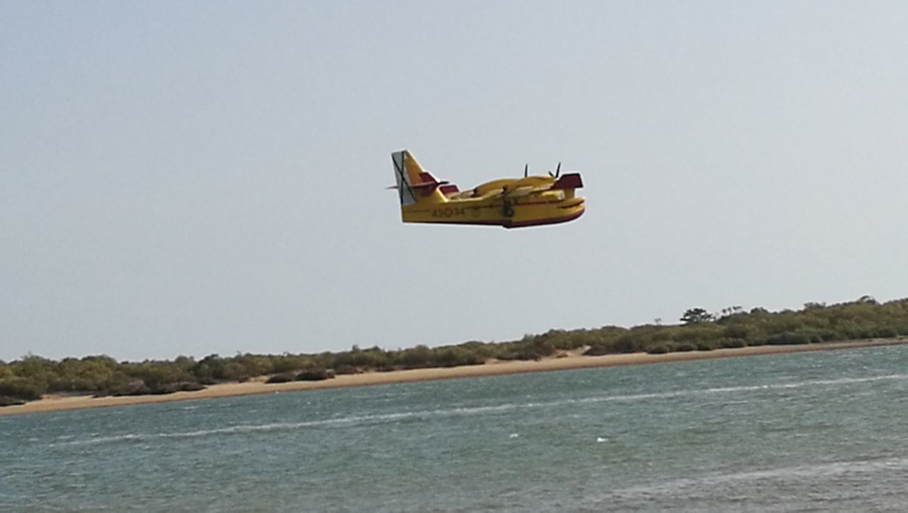 water, flying, sea, air vehicle, airplane, transportation, mid-air, clear sky, mode of transport, outdoors, day, helicopter, nature, waterfront, beach, sky, nautical vessel, adventure, no people, plane