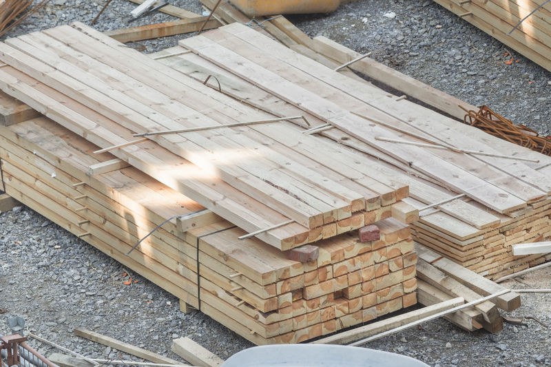 Stacked wooden boards at a construction site. Pile Board Carpentry Close-up Day High Angle View Indoors  Industry Lumber Industry No People Timber Wood - Material Wood Pile Wood Pile; Wooden Boards