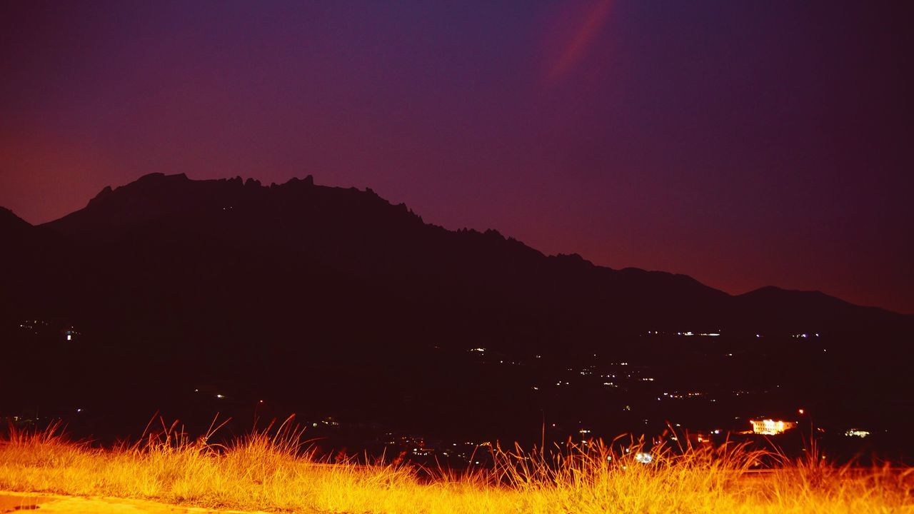night, nature, mountain, field, grass, illuminated, beauty in nature, sunset, tranquility, scenics, no people, tranquil scene, outdoors, landscape, burning, silhouette, mountain range, clear sky, sky