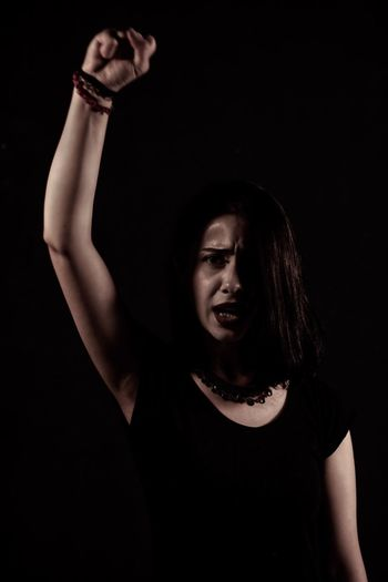 Portrait of young woman with arm raised standing against black background