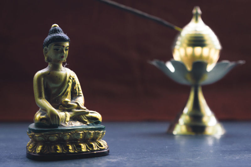 Close-up of buddha statue on table in temple