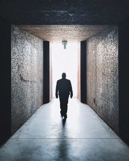 Rear view full length of man walking in passage amidst walls