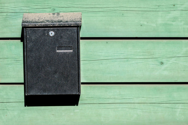 Close-up of closed mailbox on wooden floor