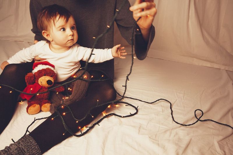 baby christmas time Light Strings Christmas Christmastime Soft Toy Mother EyeEm Selects Child Childhood Baby One Person Indoors  Young Innocence Toy Real People Babyhood Home Interior Front View Cute Holding Toddler  Baby Clothing