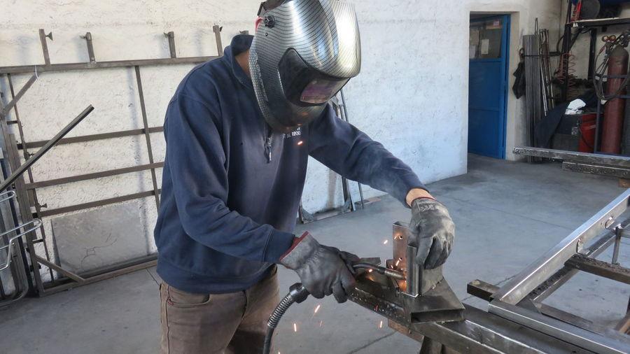 Worker welding metal at factory
