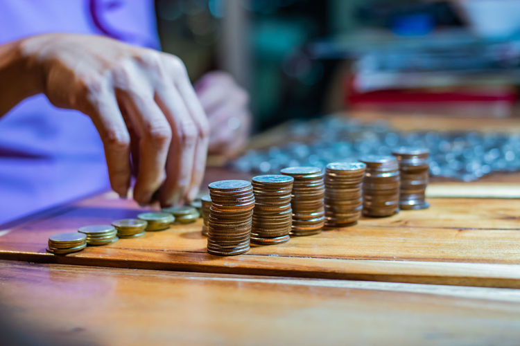 Many coins on a wooden table. Arrangement Business Coin Counting Currency Economy Finance Finger Hand Human Body Part Human Hand Indoors  Investment Large Group Of Objects Midsection One Person Savings Selective Focus Stack Table Wealth Wood - Material