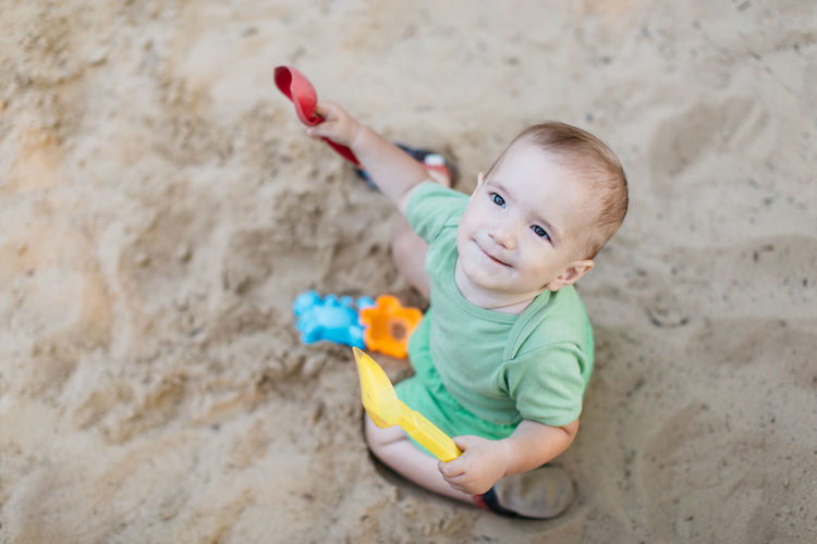 Little child in sandpit. Portrait of happy little baby boy enjoying playing with sand toys on summer day. Baby Babyhood Sand Sandpit Summer Infant Child 1 Year Old Boy Caucasian Childhood One Person Outdoors Real People Montessori Playing Playground Happy Top View From Above  Spade Yellow Outside Face Smiling