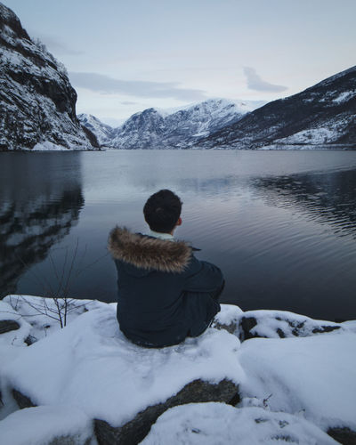 Rear view of man on snowcapped mountains during winter