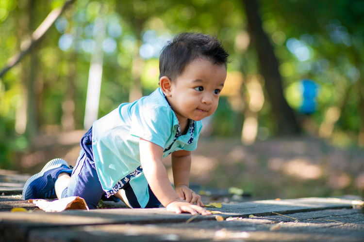 Cute boy looking away while crawling on land