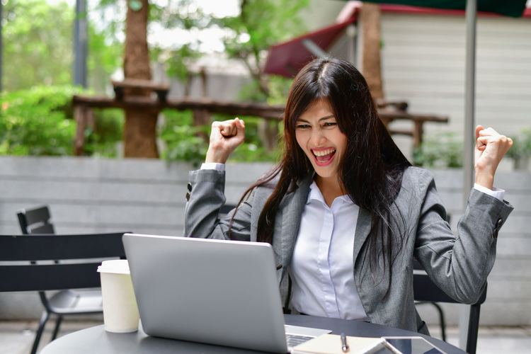 Adult Business Communication Computer Connection Emotion Front View Hair Hairstyle Laptop One Person Outdoors Real People Sitting Smiling Table Technology Using Laptop Wireless Technology Women