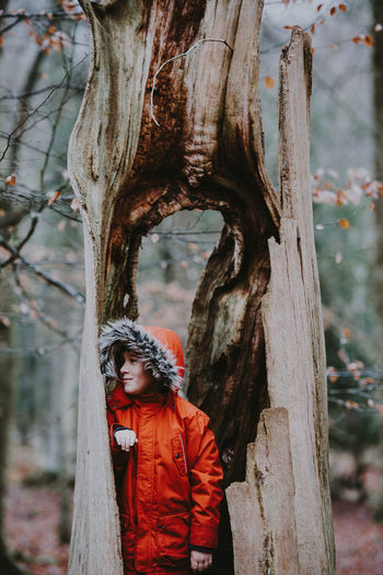 Boy resting on an old tree trunk wearing a red coat in Winter Boy Child Childhood Childhood Memories Day Focus On Foreground Innocence Kid Leisure Activity Lifestyles Nature One Person Outdoors Plant Real People Standing Tree Tree Trunk Trunk