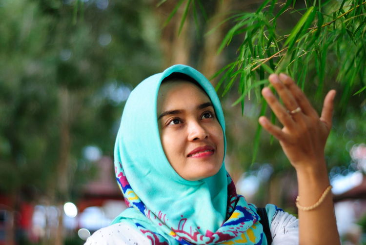 Close-up of woman wearing hijab looking at plant in park