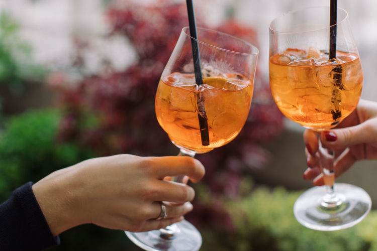 Human Hand Refreshment Drink Alcohol Hand Food And Drink Human Body Part Holding Glass Celebration Real People Friendship Focus On Foreground Celebratory Toast Smiling Togetherness Wine Two People Lifestyles Close-up Body Part Finger Aperitif Aperol Spritz Women