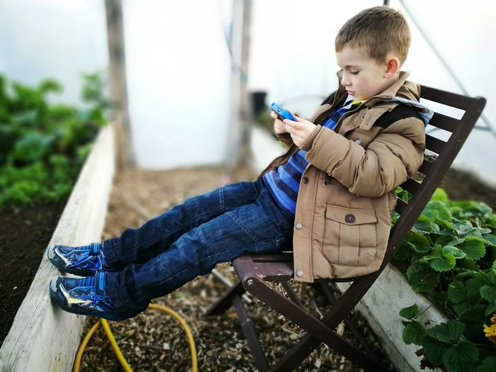 Side View Of Boy Playing Video Game While Sitting On Chair In Yard