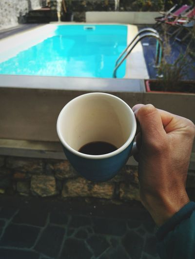 Midsection of person holding coffee cup at swimming pool