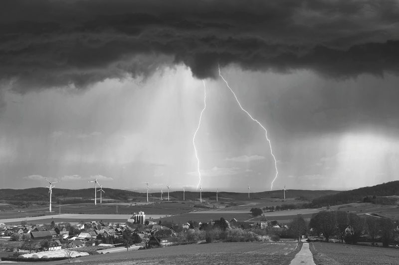 Panoramic view of lightning over sea against storm clouds