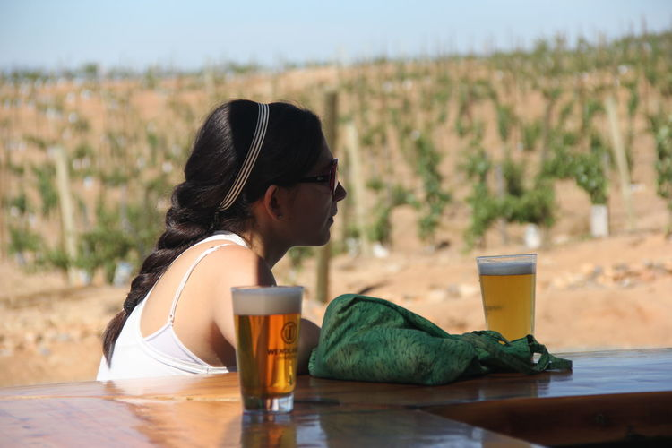 Side view of young woman by beer on table against vineyard
