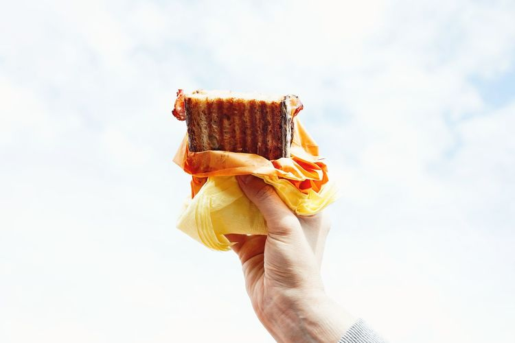 Cropped hand holding sandwich against cloudy sky