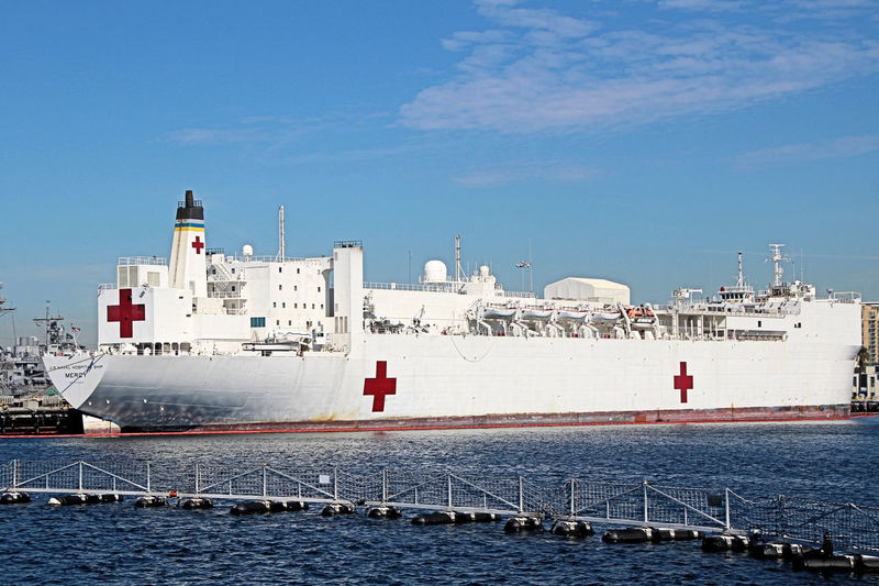 """The USNS Mercy's primary mission is to provide rapid, flexible, and mobile acute medical and surgical services to support Marine Corps Air/Ground Task Forces deployed ashore, Army and Air Force units deployed ashore, and naval amphibious task forces and battle forces afloat. Secondarily, she provides mobile surgical hospital service for use by appropriate US Government agencies in disaster or humanitarian relief or limited humanitarian care incident to these missions or peacetime military operations. USNS Mercy, homeported in San Diego, is normally in reduced operating status. Her crew remains a part of the staff of Naval Medical Center San Diego until ordered to sea, at which time they have five days to fully activate the ship to a NATO Role III Medical Treatment Facility, the highest only to shore based fixed facilities outside of the theater of operations. Like most """"USNS"""" Ships, Mariners from the US Navy's Military Sealift Command are responsible for navigation, propulsion, and most deck duties on board. Mercy is, as of 2012, part of MSC's Service Support Program. However, the """"Medical Treatment Facility"""", or hospital on the ship, is commanded by a Captain of the Navy Medical Corps or Navy Nurse Corps. Architecture Building Exterior Built Structure Commercial Dock Day Freight Transportation Harbor Hospital Ship, USNS Mercy, Mercy, Relief, Disaster, Military, Red Cross, US Navy, San Diego, California, Port, Harbor, Bay, Industry Nature Nautical Vessel No People Outdoors Sea Ship Shipping  Shipyard Sky Transportation Water Waterfront"""