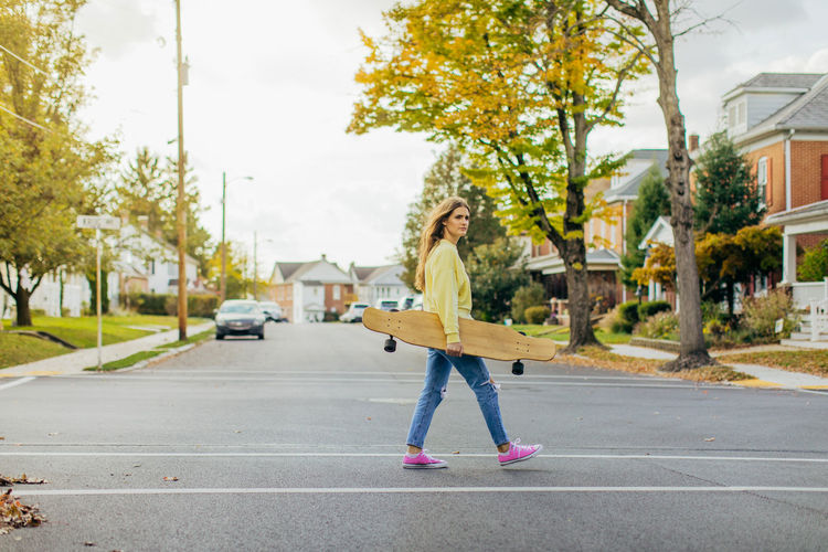 Girl crossing street in small town while holding a longboard with flowing hair