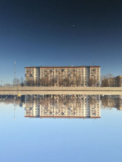 Reflection of built structure in lake against clear blue sky