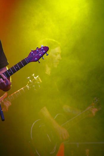 Side view of musician playing guitar seen through green smoke