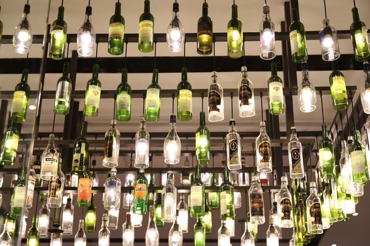 Low angle view of illuminated bottles hanging in bar