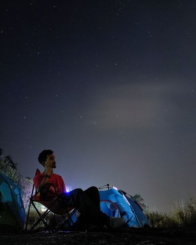 Man sitting on chair against sky at night
