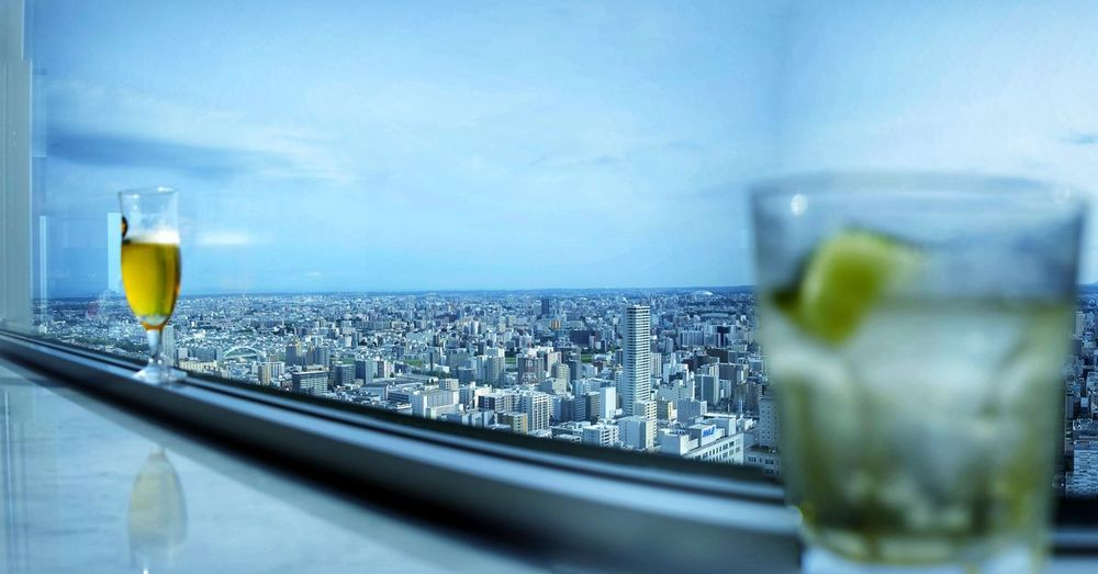 Close-up of beer in glass against cityscape